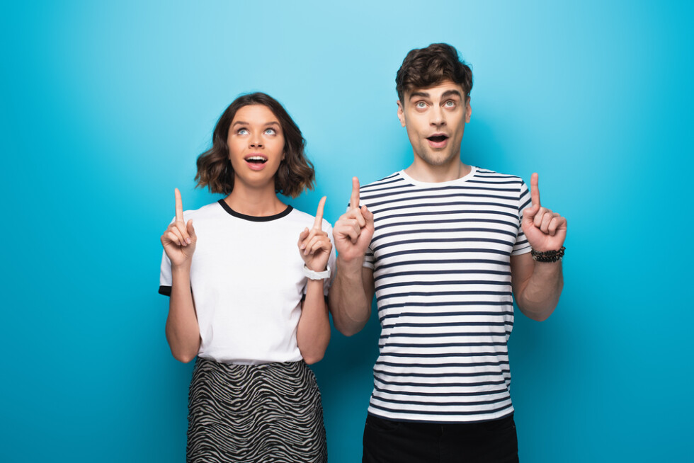 positive-man-and-woman-looking-up-and-pointing-with-fingers-on-blue-background.jpg